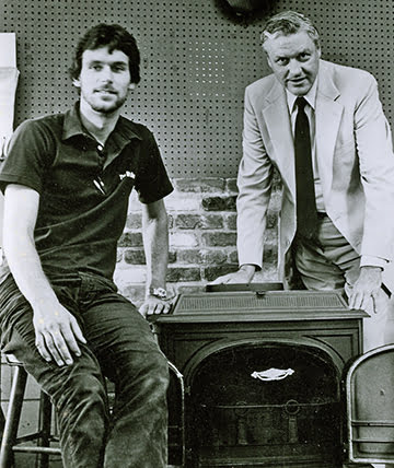 Circa 1981: Bill and his father Ted with the flagship Defiant wood stove by Vermont Castings.